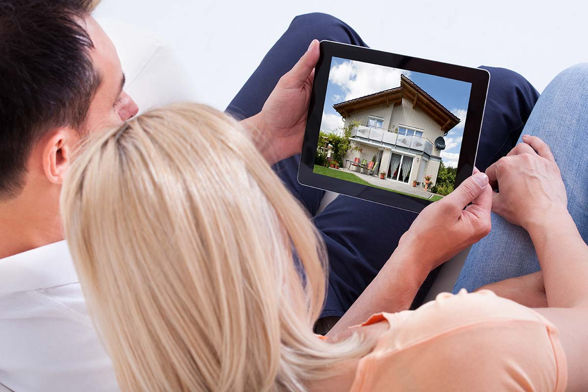 Couple looking house on tablet